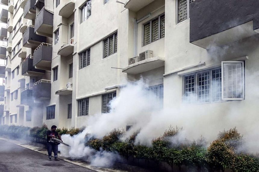 A worker sprays pesticide at an apartment block area in Kuala Lumpur on Sept 8, 2016.