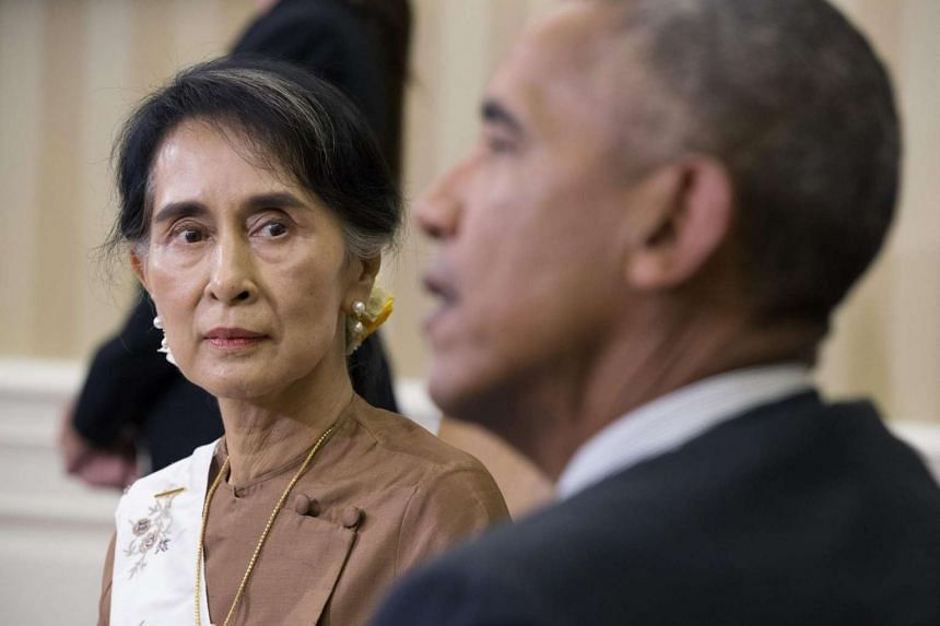 Aung San Suu Kyi listens to US President Barack Obama deliver remarks to members of the news media during their meeting in the White House on Sept 14, 2016.