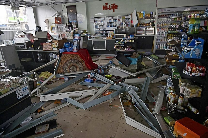 A store in Pingtung county left damaged by yesterday's storm, which was moving east at a speed of about 17kmh and packing winds of up to 227kmh in the late afternoon. A motorist braving fierce winds and rain in Kaohsiung yesterday. Meranti is expecte