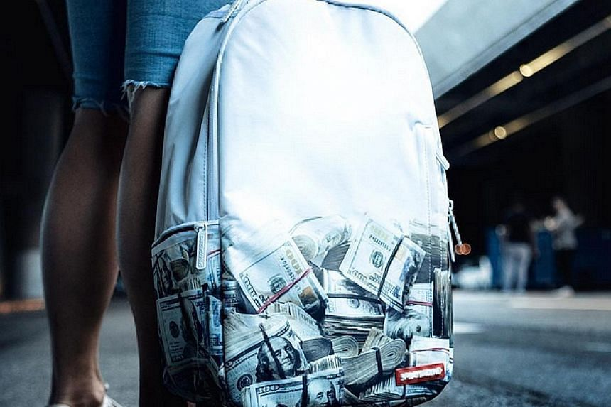 A Sprayground DLX bag emblazoned with stacks of money.