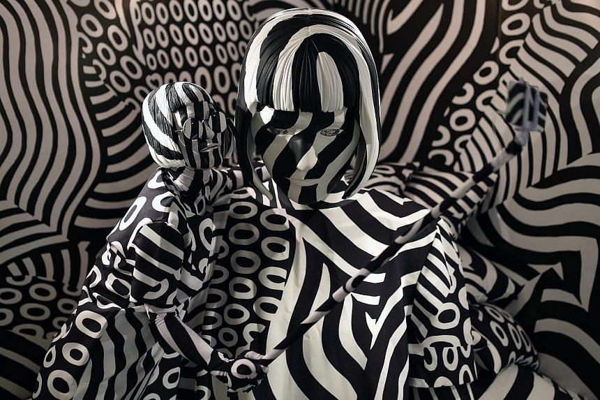 A woman (left) blending right in with Japanese painter Shigeki Matsuyama's art installation, Narcissism: Dazzle Room, during the Rooms 33 fashion and design trade show at Yoyogi National Stadium in Tokyo yesterday. Since 2000, Rooms has been a biannu