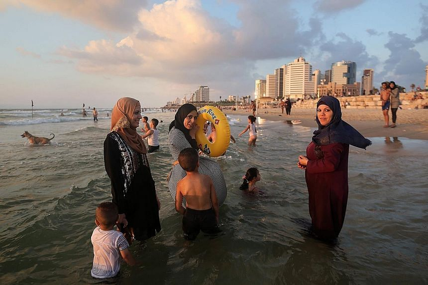 Palestinian women having a good time on the beach in Tel Aviv during the Eid al-Adha holiday on Tuesday. Thousands of Palestinians from the West Bank swam at beaches in and around the Israeli commercial capital Tel Aviv, after being granted permits t