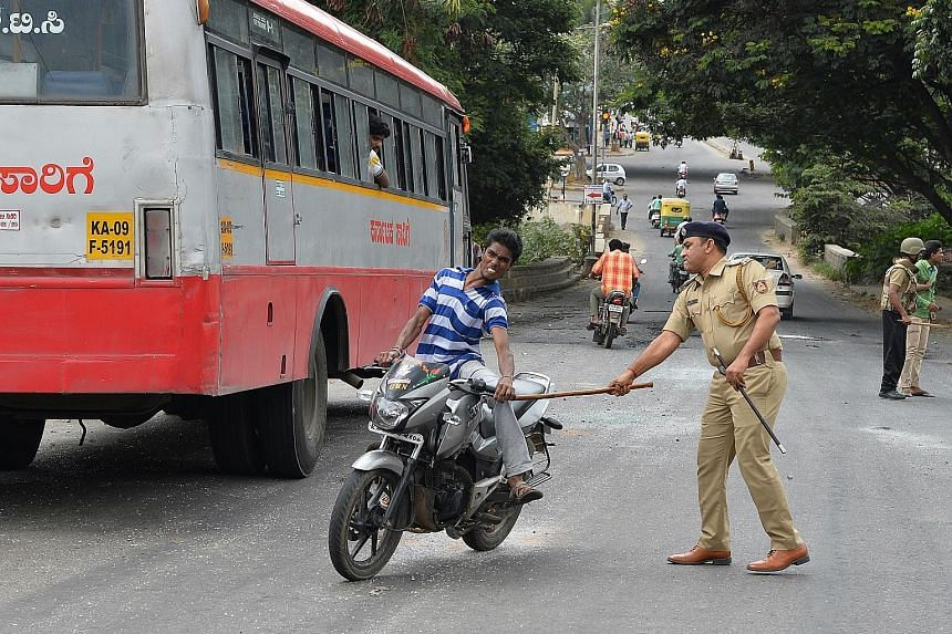 A policeman hitting a motorcyclist during a curfew in Bangalore on Tuesday. Violent protests erupted over the sharing of water from the Cauvery river.