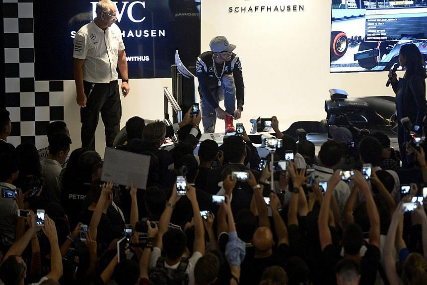 Lewis Hamilton tying his laces on stage after driving a race-car simulator during his public appearance at Marina Bay Sands. While his virtual car broke down, the Briton is certain he will not suffer the same fate as in three of the last five years.