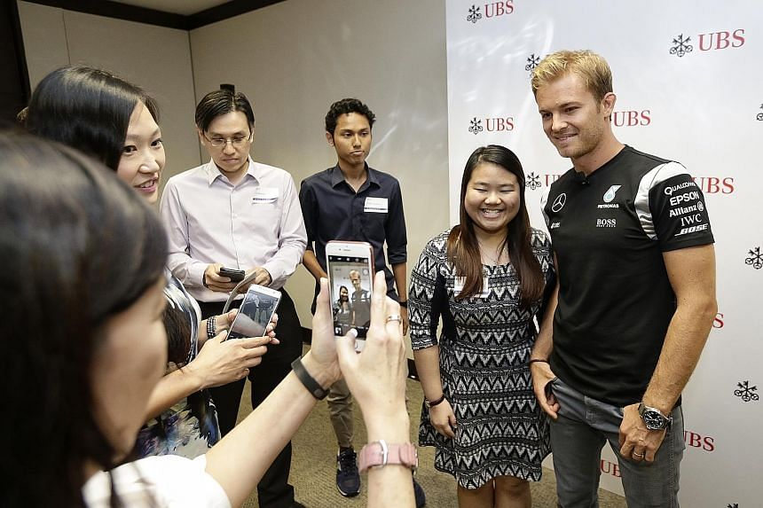 Mercedes driver Nico Rosberg taking a picture with Ms Simone Wong, a 21-year-old student and one of the winners of the ST-UBS contest.