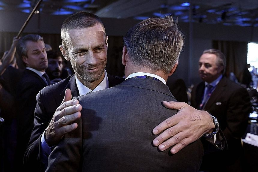 Newly elected president, Slovenian Aleksander Ceferin, is congratulated by Uefa representatives during the 12th extraordinary congress in Lagonissi, Greece. He takes over the remainder of Michel Platini's term.