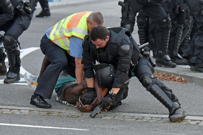 Police officers take a man into custody during a gathering at Kornmarkt square in Bautzen, Germany.