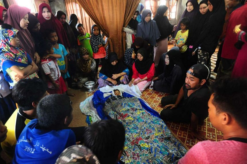 Grieving relatives gather around the body of a four-year-old girl during funeral preparations after she and her father were killed by a blast in front of a school.