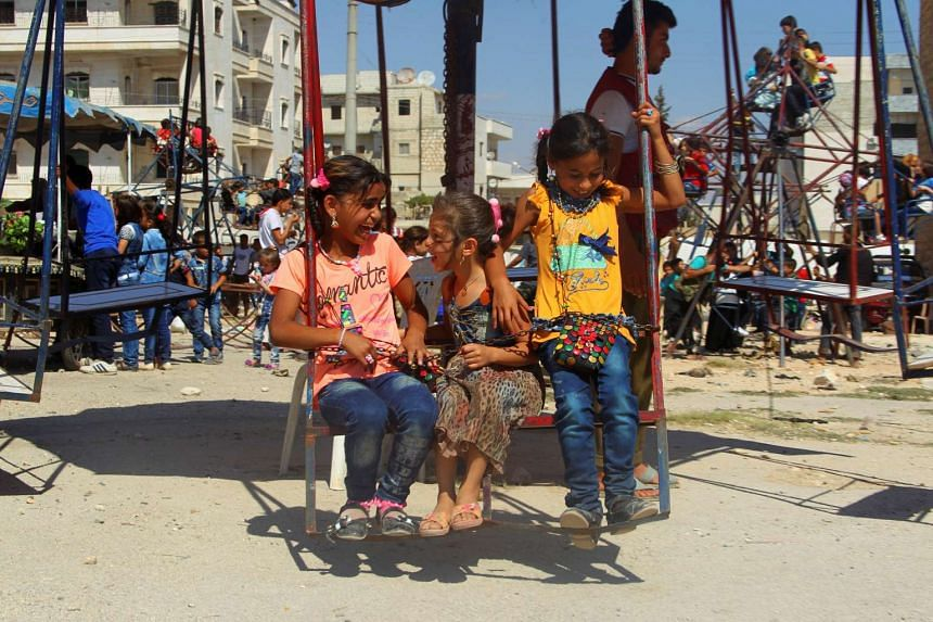 Children play on swings on the third day of Eid al-Adha in the rebel controlled city of Idlib, Syria, on Sept 14, 2016.