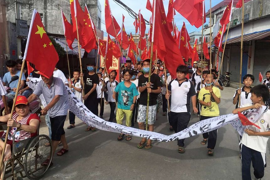 Villagers including schoolchildren take part in a protest march, demanding the release of their village chief Lin Zuluan, in Wukan, China.