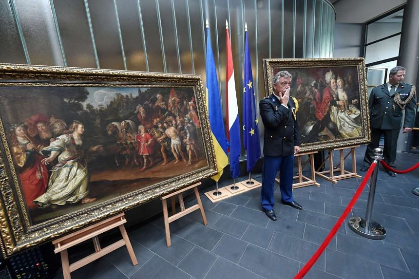 Dutch officers stand guard in front of the Return Of Jephta (left) and Lady World by Jacob Waben at the Dutch Embassy in Kiev on Sept 16, 2016.