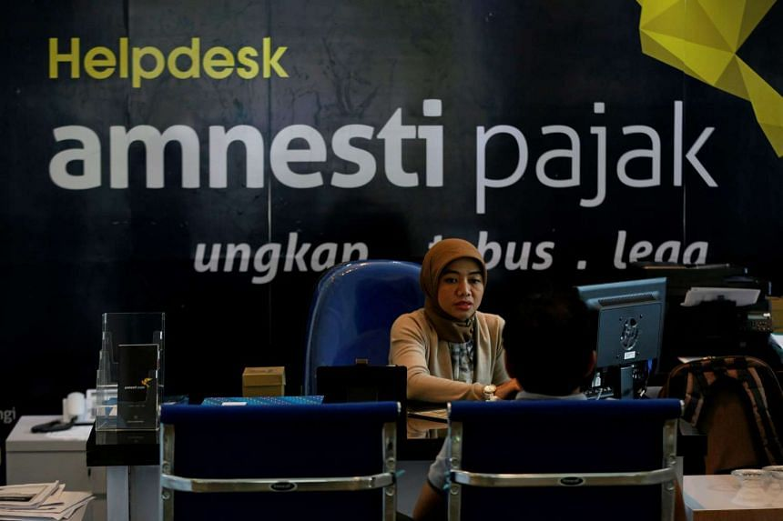 An officer assists a tax amnesty participant at a help desk inside Indonesia's tax headquarters in Jakarta on Sept 8, 2016.
