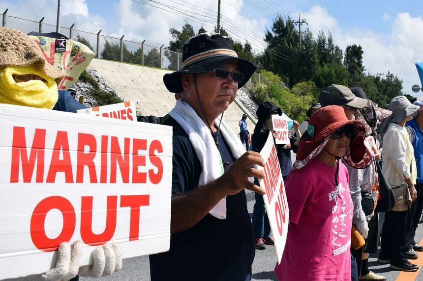 People stage a rally in front of the main gate of the Camp Schwab of the US Marine Corps in Nago, Okinawa prefecture, on Sept 16, 2016.