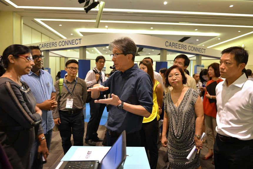Manpower Minister Lim Swee Say speaks to staff of Optimum Solutions (S) Pte Ltd during his visit to the Adapt and Grow Virtual Career Fair at e2i in Jurong.