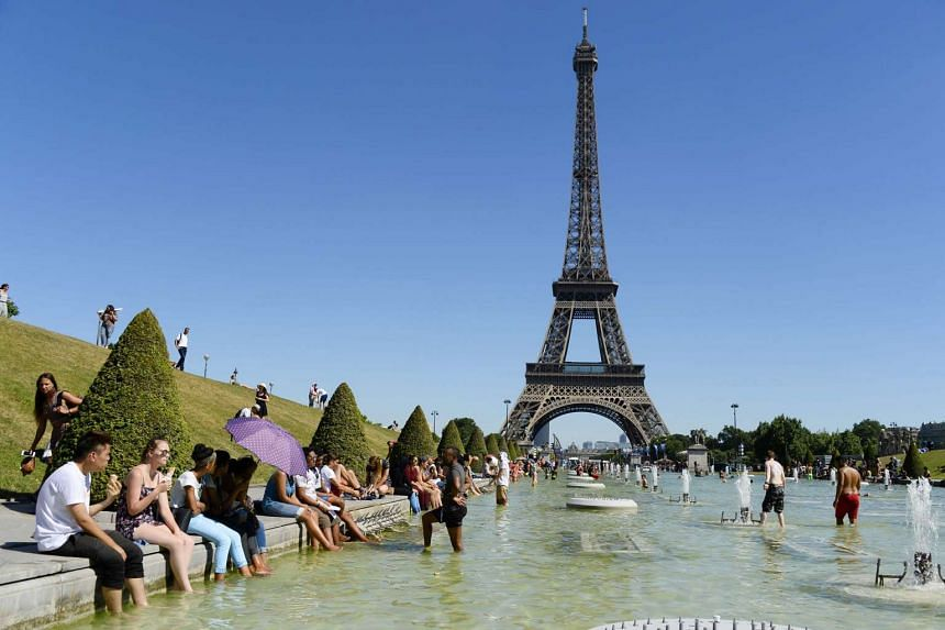 People refreshing in the water of the Trocadero fountains in front of the Eiffel tower in Paris on July 19, 2016.
