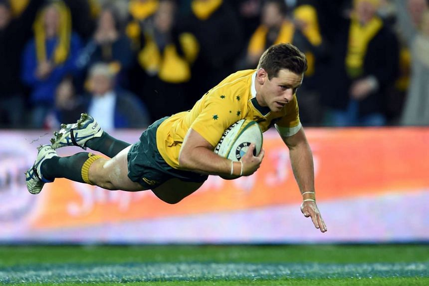 Australia's Bernard Foley dives for a successful try against England during their third and final rugby union Test in Sydney on June 25, 2016.