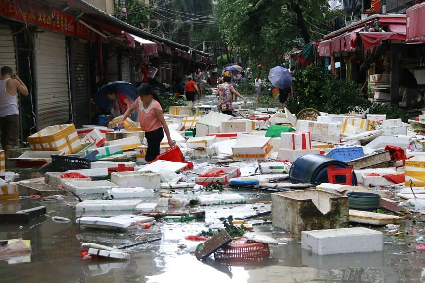 Residents clean up a flooded street in Xiamen, in China's eastern Fujian province after Typhoon Meranti made landfall on Sept 15, 2016.