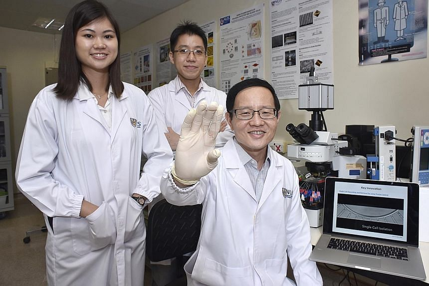 Professor Lim, 50, holding up a microfluidic chip that could pave the way for more personalised medicine when treating cancer patients. Ms Trifanny Yeo Zhi Xiang, 26, and Dr Tan, 35, are also part of the research team that designed the device.