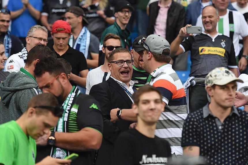 Monchengladbach's director of sport Max Eberl with fans ahead of the rearranged match against Man City on Wednesday night.