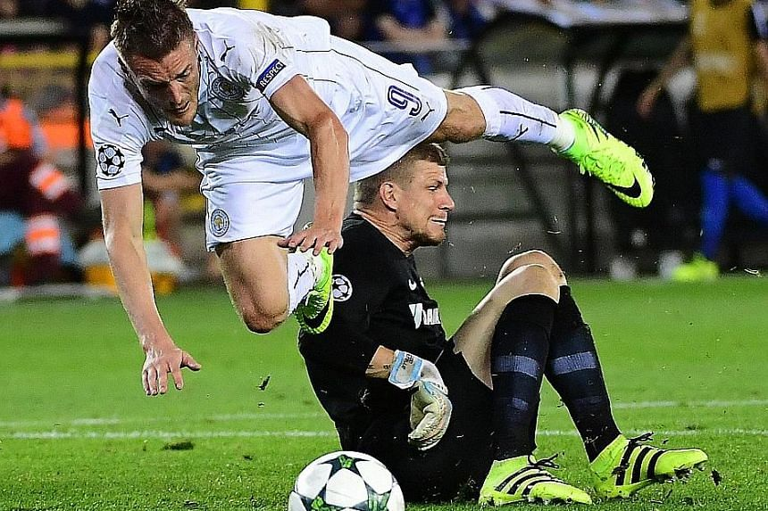 Leicester's Jamie Vardy falls after being tackled by Club Brugge goalkeeper Ludovic Butelle, resulting in a penalty. Riyad Mahrez netted for his second goal in the Champions League opener as the English champions ran out 3-0 winners.