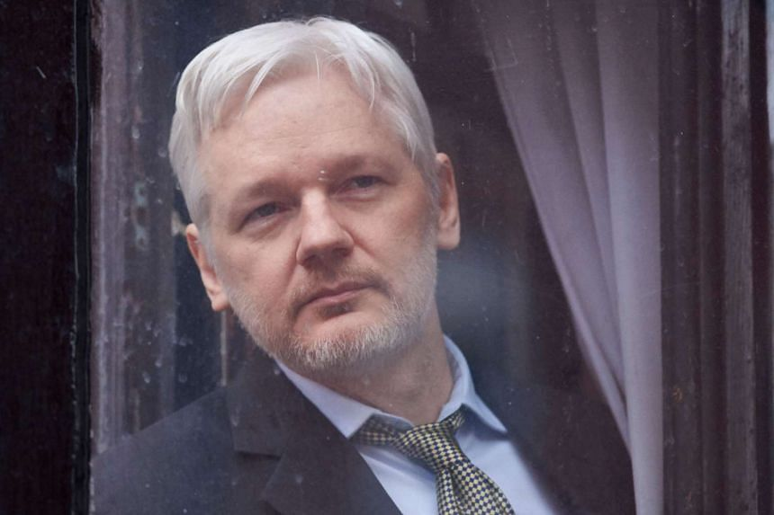 A February 2016 photo shows WikiLeaks founder Julian Assange looking out of the balcony window of the Ecuadorian embassy in London.