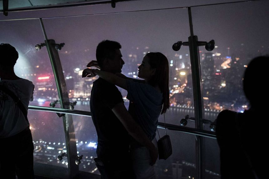 A couple embrace as they watch the view from the Oriental Pearl Tower in Shanghai on Sept 8, 2016.