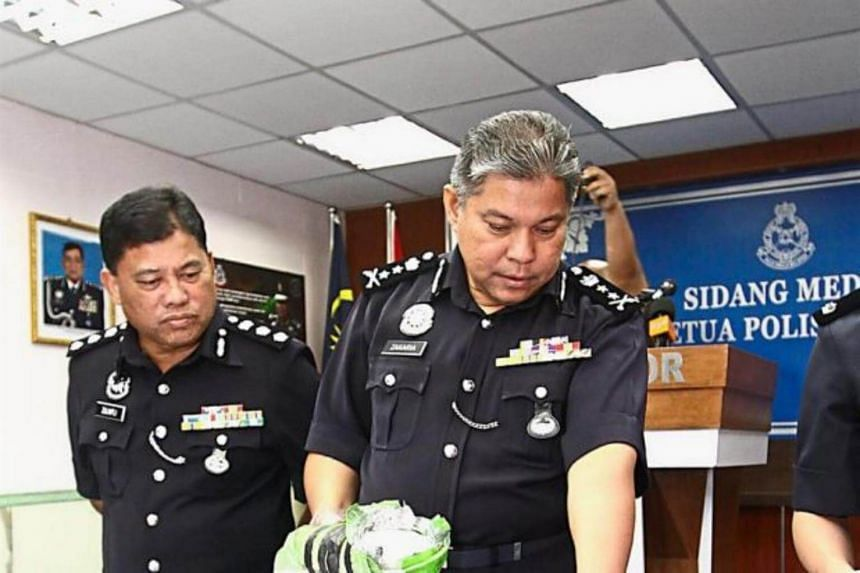 Senior Asst Comm Datuk Mohd Zakaria Ahmad showing some of the items seized from the Singaporean during a press conference at the state police contingent headquarters in Johor Baru.