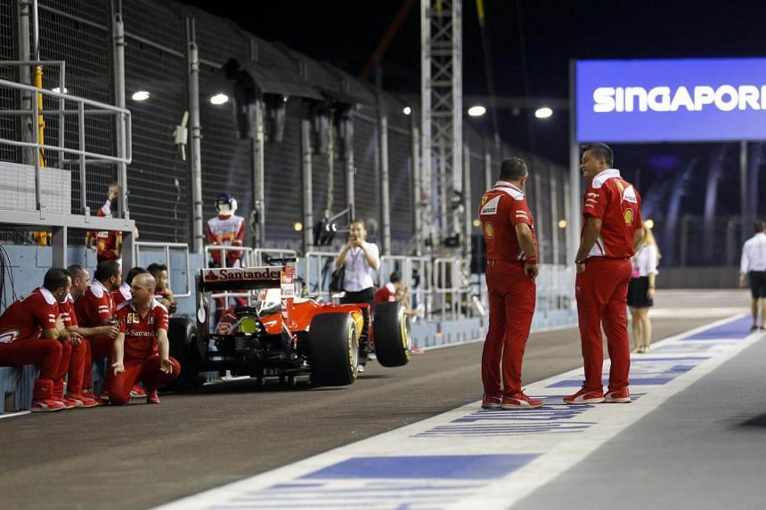 Members of Scuderia Ferrari formula one team gather near a car as they wait for inspection at the Singapore Grand Prix Marina Bay Circuit on Sept 15, 2016.