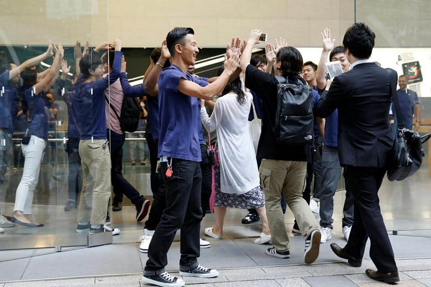 Apple Store staff share high-fives with customers who have been waiting in line to purchase Apple's new iPhone 7 and 7 Plus at the Apple Store in Tokyo's Omotesando shopping district on Sept 16, 2016.
