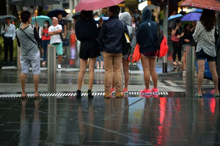 Pedestrians waiting to cross the road in Orchard Road on a rainy day.