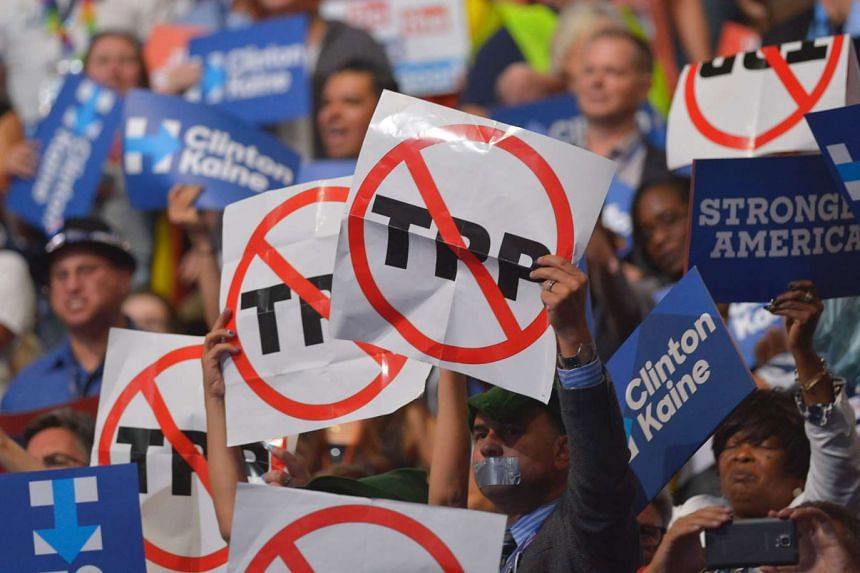 People hold signs against the Trans Pacific Partnership (TPP) at the Wells Fargo Centre on July 27, 2016.
