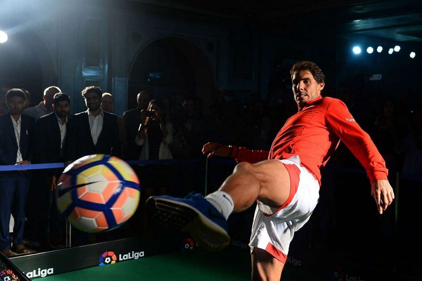Spanish tennis player Rafael Nadal plays with a football at a function to promote the Spanish football league, in New Delhi on Sept 15, 2016.