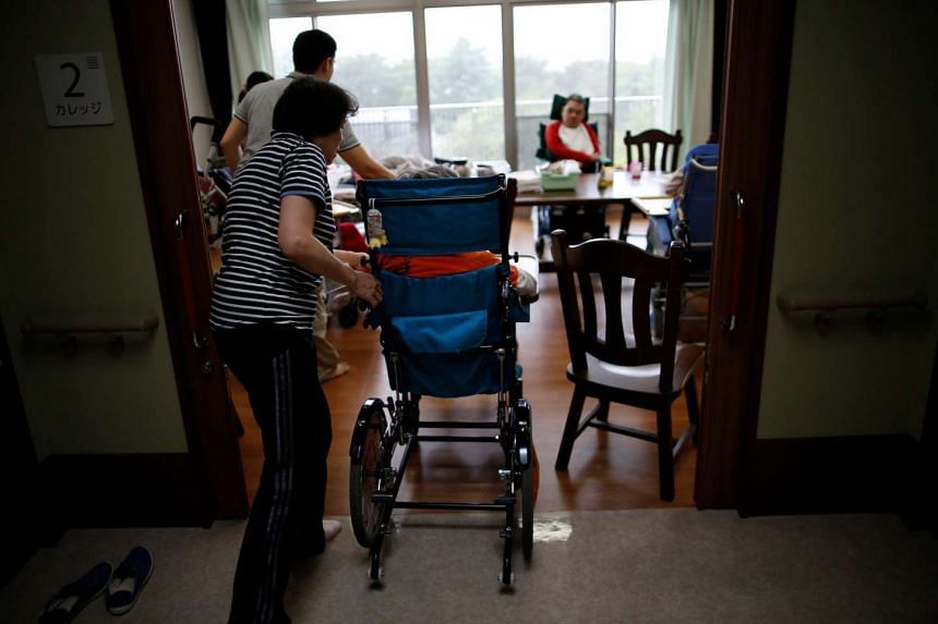 Staff members aid to move people with disabilities on wheelchairs at the National Rehabilitation Center for Children with Disabilities in Tokyo on Sept 13, 2016.