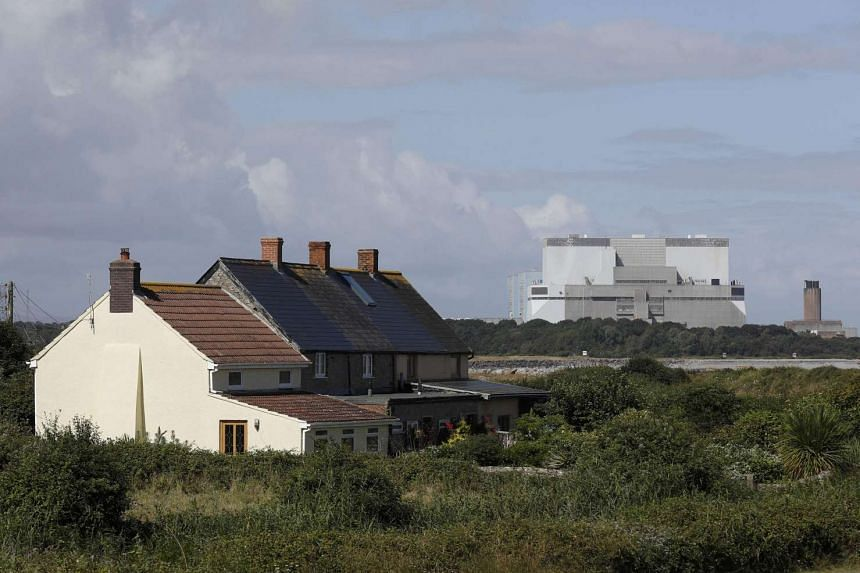 Houses stand in front of Hinkley Point A and B nuclear power stations in Britain, Aug 4, 2016.