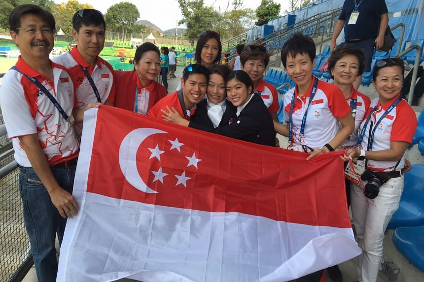 Ms Grace Fu and Singapore supporters surround the three para-riders from Singapore (from left) Maximillian Tan, Laurentia Tan and Gemma Rose Foo after Gemma and Laurentia have completed their rides.