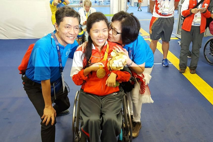 Yip Pin Xiu and her parents pose for a photo after her win at the 2016 Rio Paralympics.