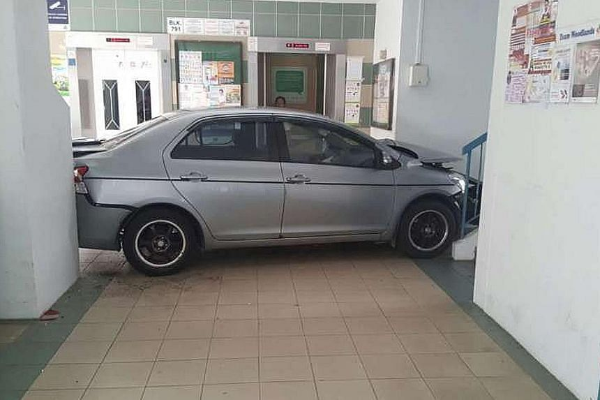 A car crashed into the void deck of a Housing Board block in Woodlands yesterday afternoon. The silver sedan was wedged between a stairwell and a wall in front of the lift lobby at Block 791, Woodlands Avenue 6. The Singapore Civil Defence Force (SCD