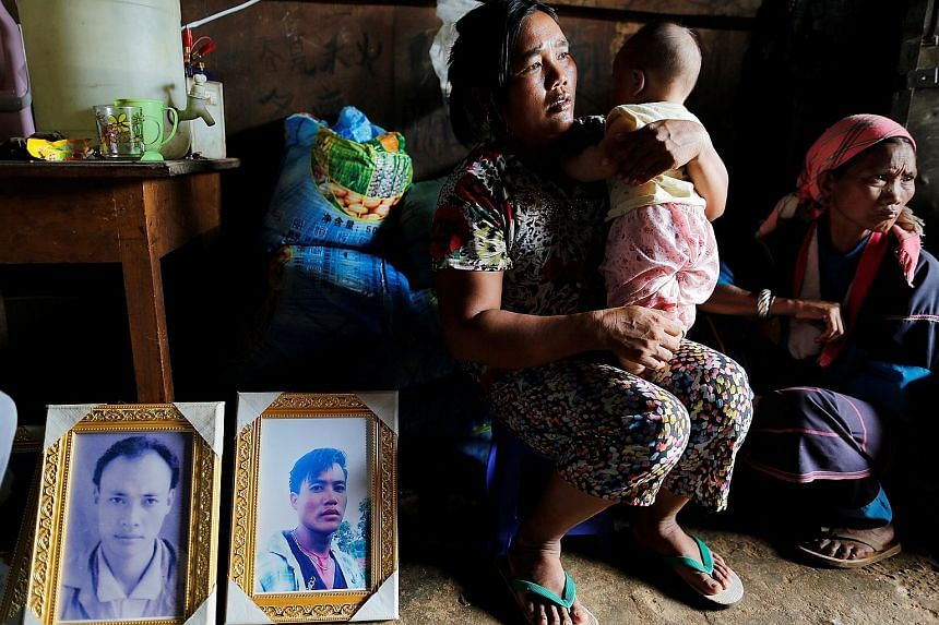 The grieving family members with two of the Mong Yaw victims' pictures in the village in Myanmar's northern Shan state in July. The two men's bodies were among five pulled from shallow graves and identified as missing villagers, after soldiers entere