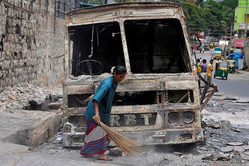 A municipal worker on Wednesday sweeping around the charred remains of a lorry that was set ablaze during violent protests in Bengaluru this week over a water dispute. Employers say the violence did no major damage to the technology hub's appeal.