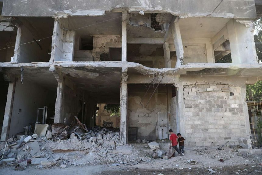 Syrian children look in the rubble of a building on the third day of the Al-Adha Eid in the rebel-controlled town of Hamouria on Sept 15, 2016.