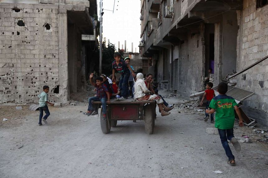 Syrian children play in the street as they celebrate the third day of the Al-Adha Eid in the town of Hamouria on Sept 14, 2016.