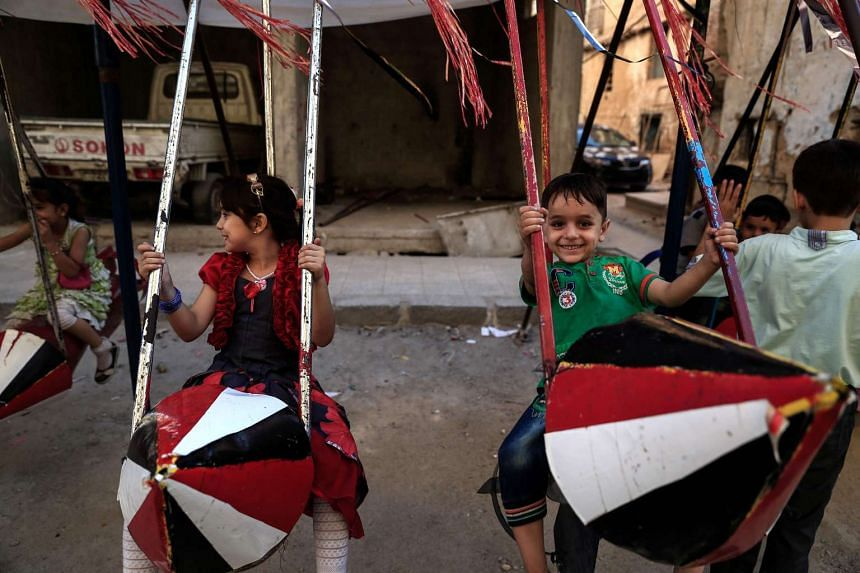 Syrian children play on swings made from the remnants of exploded rockets in the rebel-held town of Douma on Sept 14, 2016.