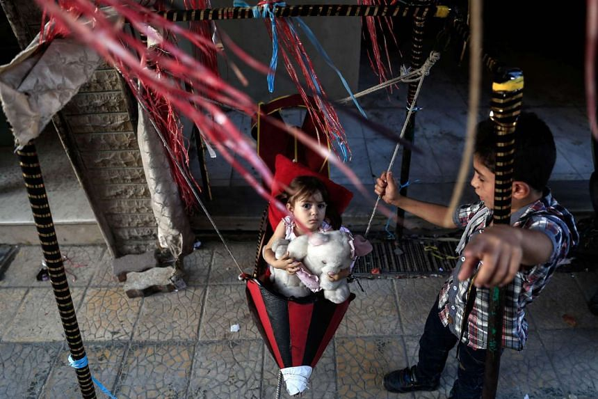 A Syrian child plays on a swing, made from the remnants of exploded rockets in the rebel-held town of Douma on Sept 14, 2016.