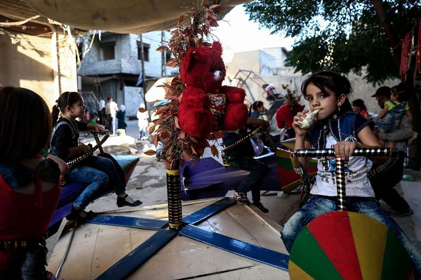Syrian children ride on toys, made from the remnants of exploded rockets in the rebel-held town of Douma on Sept 14, 2016.