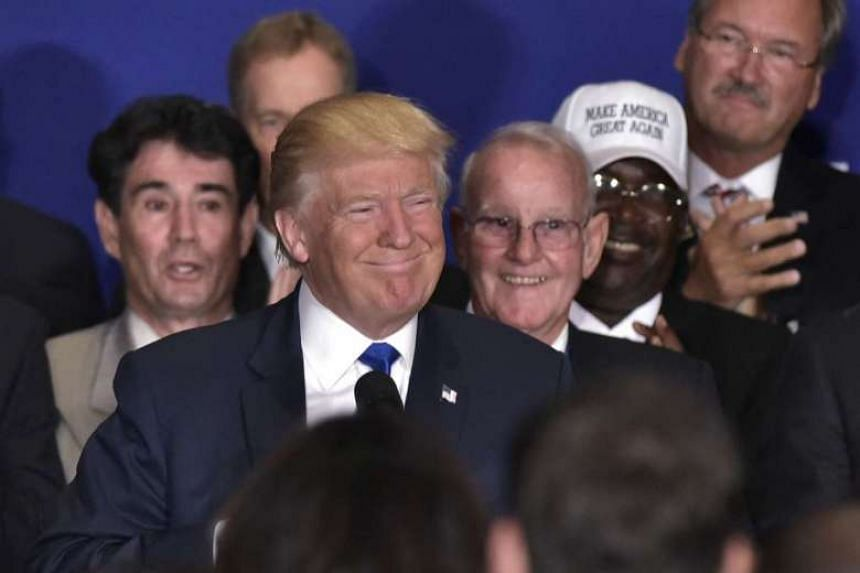 Donald Trump smiles as he arrives on stage for a press conference on Sept 16, 2016.