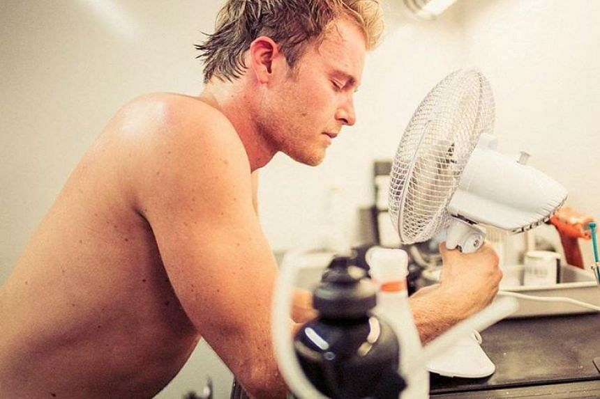 Formula One driver Nico Rosberg cools off in front of an electric fan in Singapore.