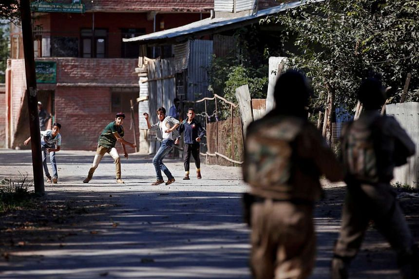 Youths hurl stones towards the Indian police during a protest against the recent killings in Kashmir, on Sept 16, 2016.