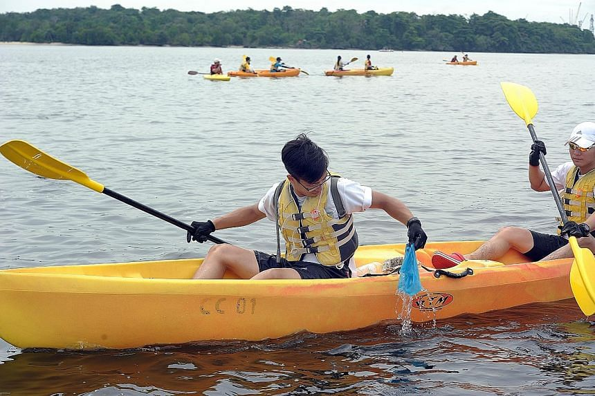Volunteers, including secondary school students, on kayaks doing their part to clear garbage from Singapore's waters yesterday as part of International Coastal Cleanup Day. During a three-hour trip from Sembawang Beach to Seletar Island, the group co