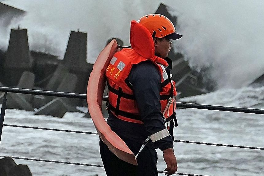 A Taiwanese Coast Guard officer patrolling a harbour in Yilan county as Typhoon Malakas approaches eastern Taiwan. Malakas is not expected to make landfall in Taiwan.