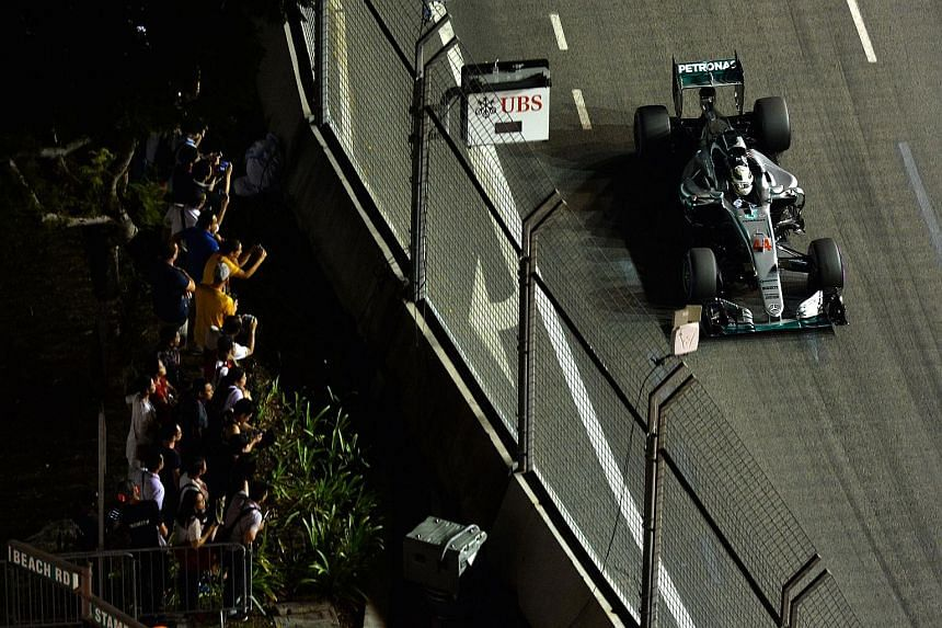 Far left: Fans cheering as Mercedes' world champion Lewis Hamilton approaches Turn 9 during qualifying, as seen from Swissotel The Stamford. Left: The contrast in mood is clear between Mercedes team-mates Nico Rosberg, waving to the media and fans af